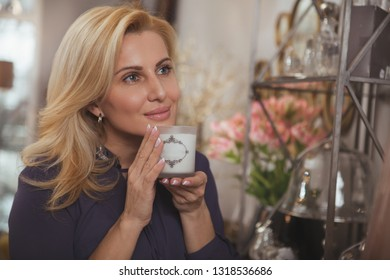 Close up of a gorgeous mature elegant woman smelling aromatic candle, while shopping at homeware store. Charming woman buying candles at home decor shop, copy space. Coziness, lifestyle concept
