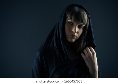 Close up of gorgeous young woman posing with blue shawl on her head. Beautiful witch looking aside with serious expression. Isolated on blue background. Concept of dark beaut and mystery.