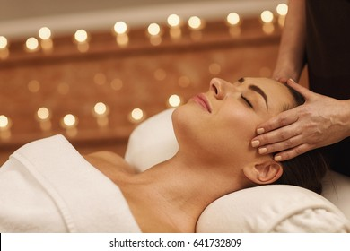 Close up of a gorgeous young woman smiling with her eyes closed enjoying head massage at spa center professional therapy health stress treatment pampering facial beauty skin recreation leisure service