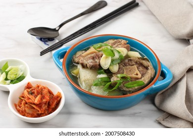 Close Up Gori Gomtang (Sokkori Gomtang) or Korean Beef Oxtail Stew  Soup, Served in the Blue Bowl with Kimchi and Sliced Green Onion - Shutterstock ID 2007508430