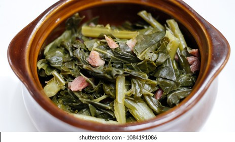 Close up of gourmet cooked collard greens and ham in a bowl with a white background