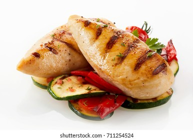 A close up of a gourmet dish with grilled chicken breast, zucchini and capsicum on a white background with copy space.