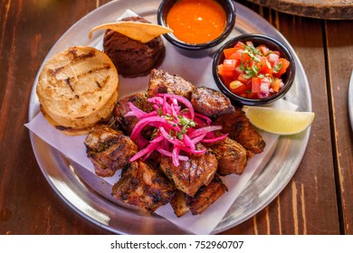 Close up Gourmet Grilled Pork Rib and Fried Potato Wedges on wood Plate with Sauce, tortillas, sauces and beans
