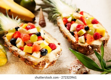 Close up Gourmet Healthy Fresh Tropical Fruit Salads in Pineapple Boats on White Sand with Sea Shells.