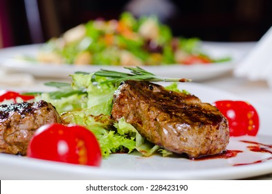 Close up Gourmet Main Course - Grilled Tender Juicy Meat with Veggies and Rosemary on White Plate. A Rich in Protein Recipe.