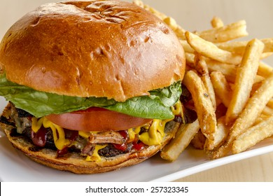 Close up of gourmet pub hamburger with bacon on white plate with side of french fries sitting on wooden table