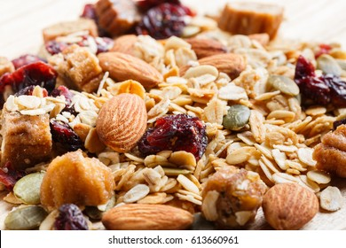 Close up granola or muesli on wooden table, dehydrated fruit mix, healthy food, almond, sun dried cultivated banana, cranberry, cashew nut, pumpkin, melon seed