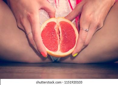 Close up of an grapefruit between woman's legs. metaphorically, image