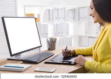 Close up of a graphic designer at work. She is wearing a yellow jacket and sitting at her computer with a large monitor. Mock up