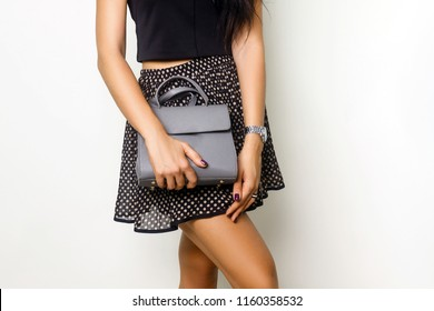 Close up of gray leather handbag in hand of stylish woman, studio shot on gray background. Female fashion and accessories.