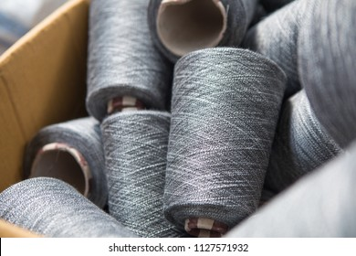 Close up gray silver yarn threads spools bobbin tubes