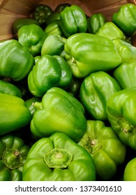 close up of green bell peppers in bushel basket
