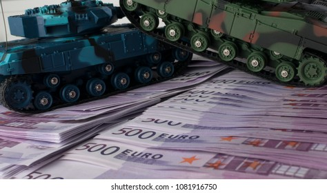 Close up green and blue tank toy placed on euro banknotes pile. business and economy war. new world war from business and economy concept. Concept of expense and cost of war.