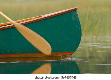 Close up of a green canoe in the water with its paddle splashing water