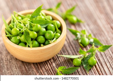 Close up green circle chilli or cherry peppers in wood bowl on table plank background