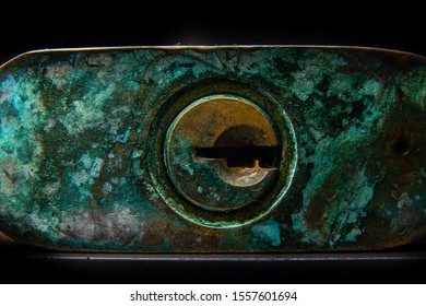 close up of green dirty and rustic key hole in dark background