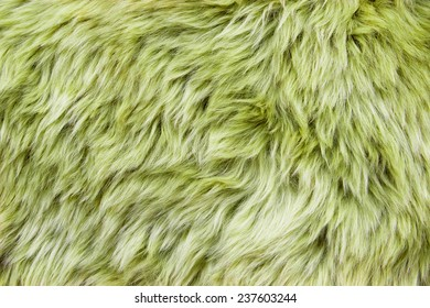 Close up of a green dyed sheepskin rug as a background