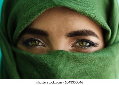 close up of green eyes of a girl with face wrapped in a green scarf