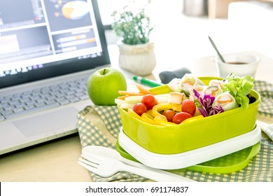 Close up green Lunch box on work place of working desk ,Healthy eating clean food habits for diet and health care concept