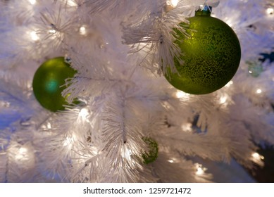 Close up of green ornaments on a white Christmas tree