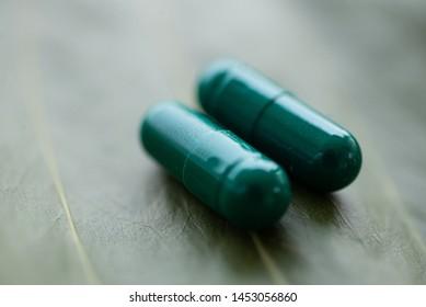 Close up Green pills on herb concept.