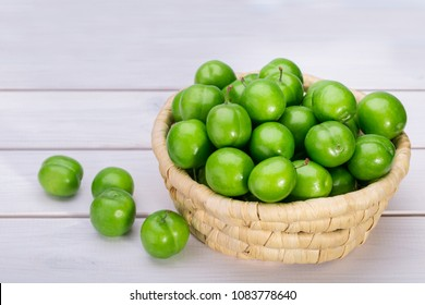 Close Up Of Green Plums Or Greengage In A Basket Isolated On White Wooden Background, Popular Spring Fruits With A Very Sharp Sour Taste Originated In Iran