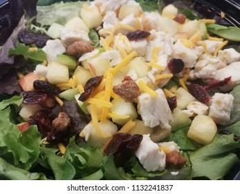 close up of green salad with chicken, cheese, and fruit