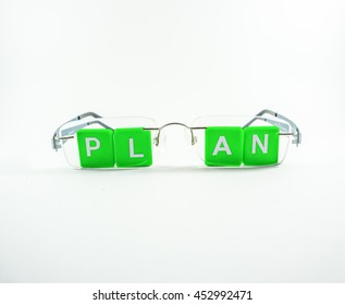 Close up Green Scrabble Letter Tiles for Plan Concept, behind eyeglasses isolated on white background. Concept of thinking abound plan.