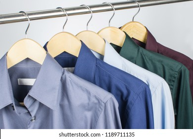 Close up green shirts or business clothes on wooden hangers, People concept, Set of mans fashion and accessories. Casual or formal tshirt. Upper section row of different coloured suit. Red, Blue, Gray