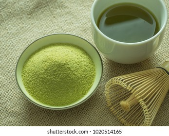 close up green tea, matcha power and whisk a cup of hot green tea on wooden table.traditional japanese drink