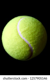 Close up of green tennis ball on black background