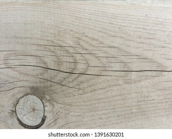 Close up of a grey brown weathered wooden wall, floor, or signage board with knots and patterns - textured background
