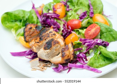 Close up of grilled chicken breast with vege and baby tomatoes.