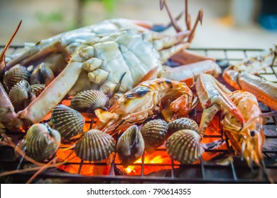 Close up grilled crabs and clams on fire charcoal stove at night party. Seafood barbecue party with crabs and clams are grilling on fire. Seafood BBQ concept, selective focus.