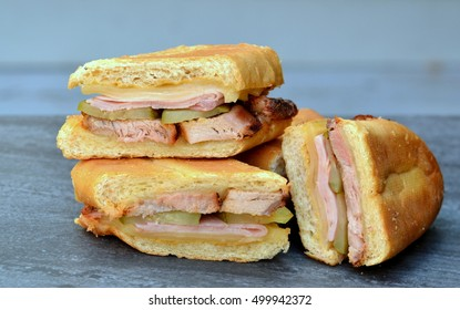 Close up of grilled Cuban Sandwiches (Cubanos) on a grey background. Made with pork, ham, Swiss cheese, pickles and mustard.
