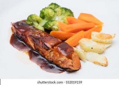 Close up of grilled salmon with barbecue sauce, potato, carrots & broccoli.