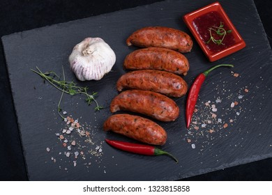 Close up of grilled sausages on black stone plate with garlic, chilli and sause