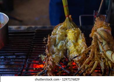 Close up grilling sliced lobster on grille.