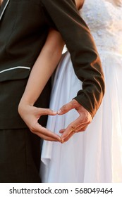 close up groom and bride hands in shape of love heart.