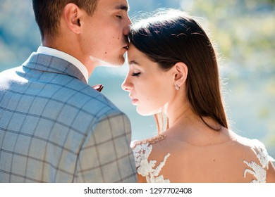 Close up groom kissing bride on forehead while standing near the lake in the mountains