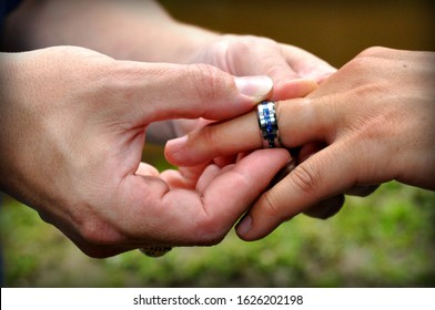 Close up of a groom putting a ring into his partner's finger