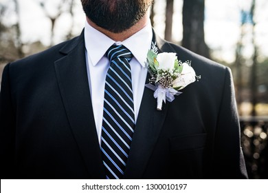 ea3b39678364 Close up of groom wearing dark suit and blue tie with white boutonniere for  wedding day