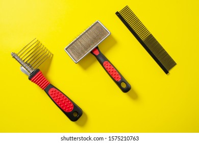 Close up grooming brush, special professional comb and furminator, for dogs and cats grooming. On bright yellow background. Concept of pets hair care and treatment, copy space.