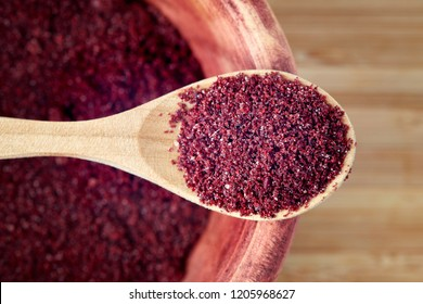 Close up of ground sumac spice powder in wooden spoon