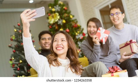 close up group of asian friends using smartphone and take selfie for party group shot in living room with pine tree christmas decoration prepare for celebration festival , relationship cocnept