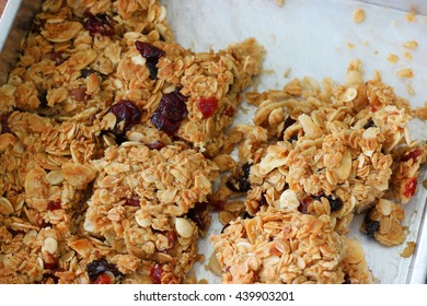 Close up to a group of baked home made muesli bars on the aluminum tray. selective focus on the middle one.