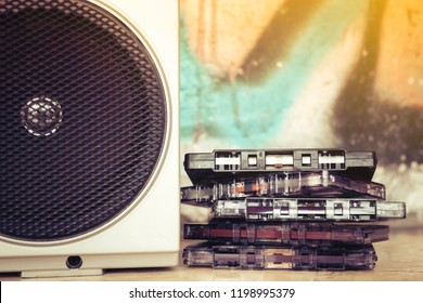 Close up of a group of cassettes stacked next to the speaker of an old boom box and on a graffiti background. Listening to the music of the past.