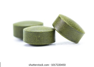 close up of a group of fermented chlorella tablets isolated on a white background