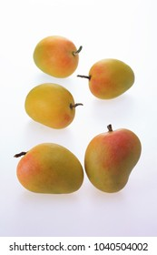 close up group of five ripe indian alphonso mangos isolated on white background