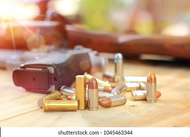 close up group in flare light and pistol with bullet on table wooden for outdoor sport and hunting,short gun semi automatic,hunting sport equipment